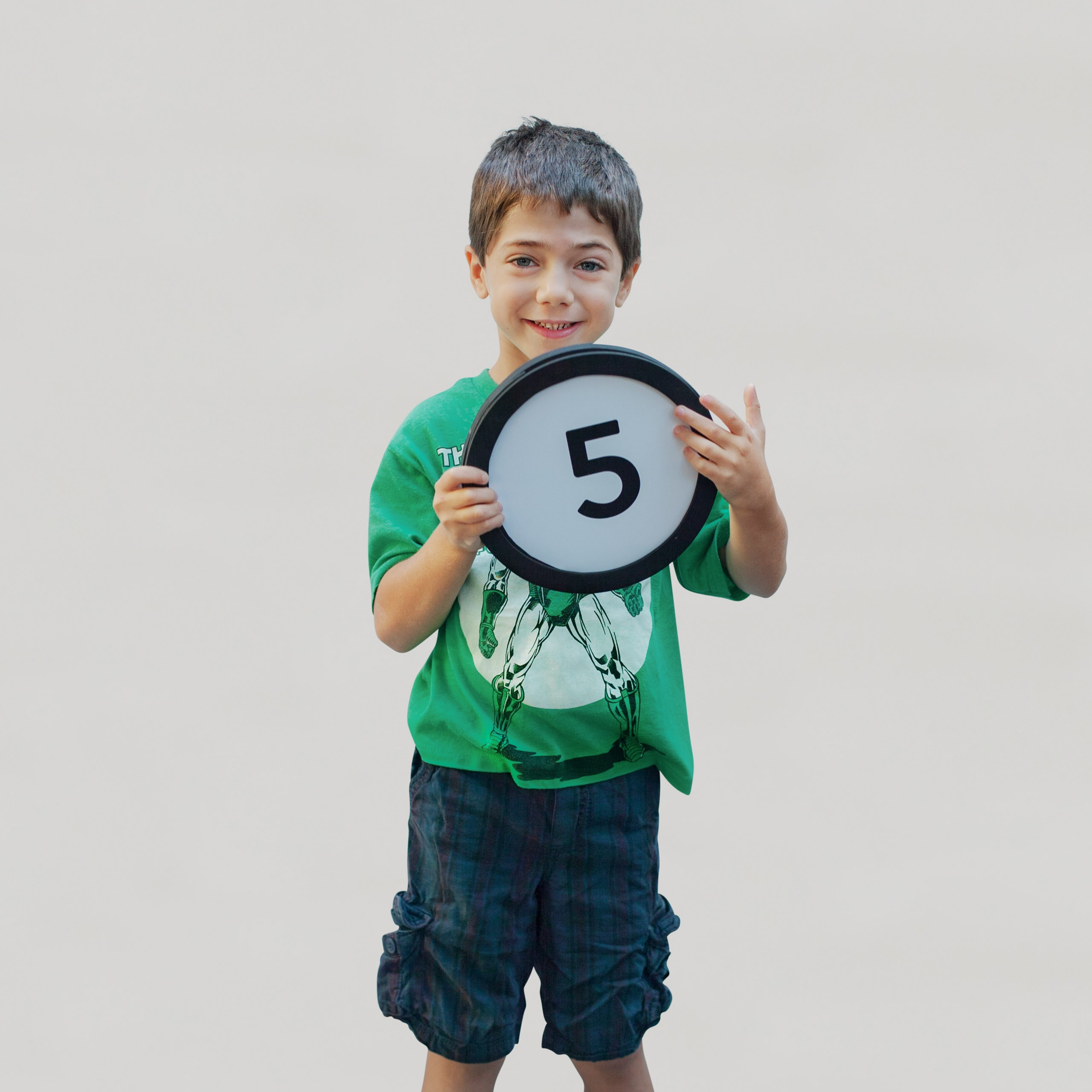 5 year old boy smiles and holds a token with the number 5 on it. This digital image is part of the 1 to Infinity portrait photography series by Danny Goldfield.