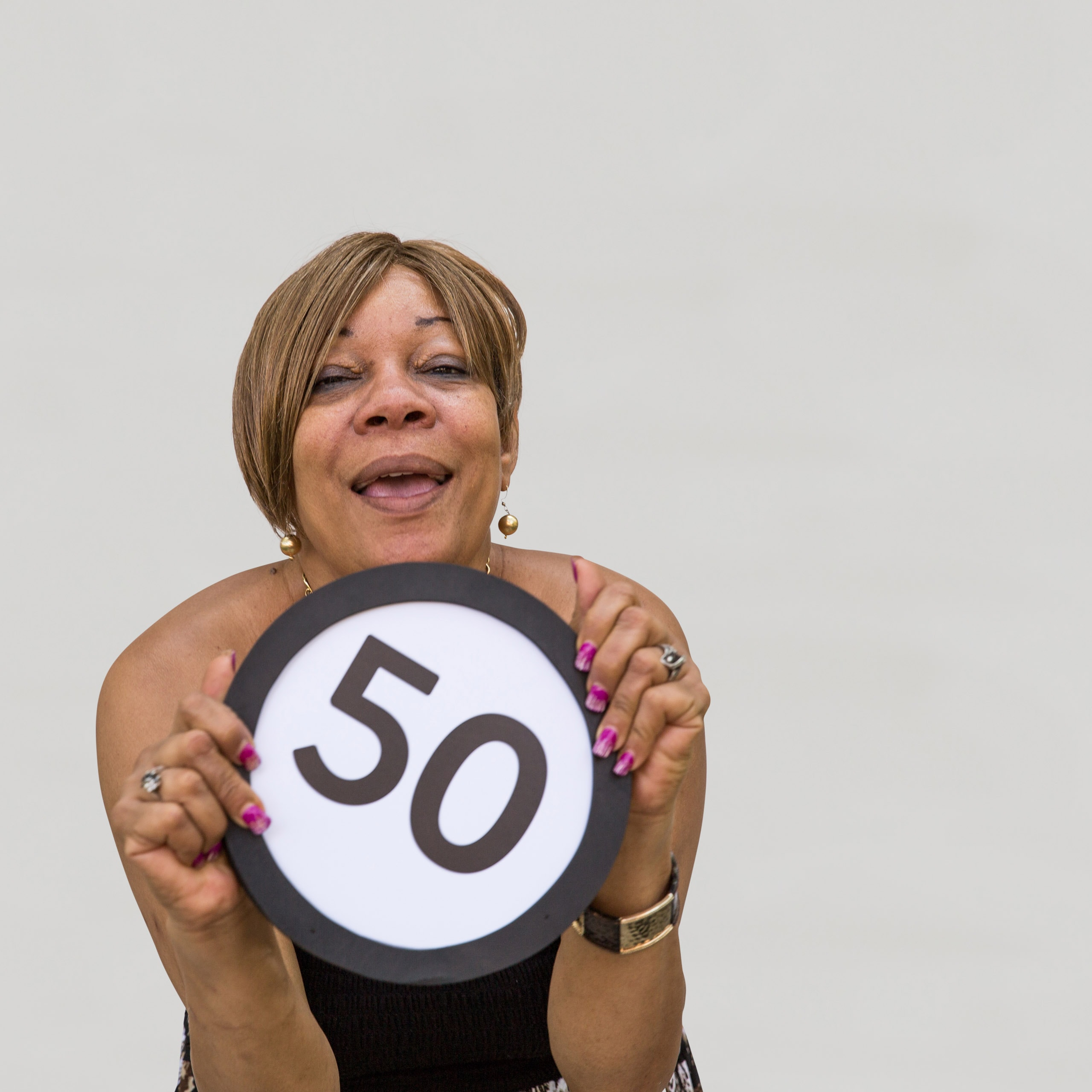 50 year old woman with an open smile laughs and looks into the lens with her eyes softly closing. With magenta painted fingernails she clutches a token in front of her body with the number 50 on it. This digital image is part of the 1 to Infinity portrait photography series by Danny Goldfield.