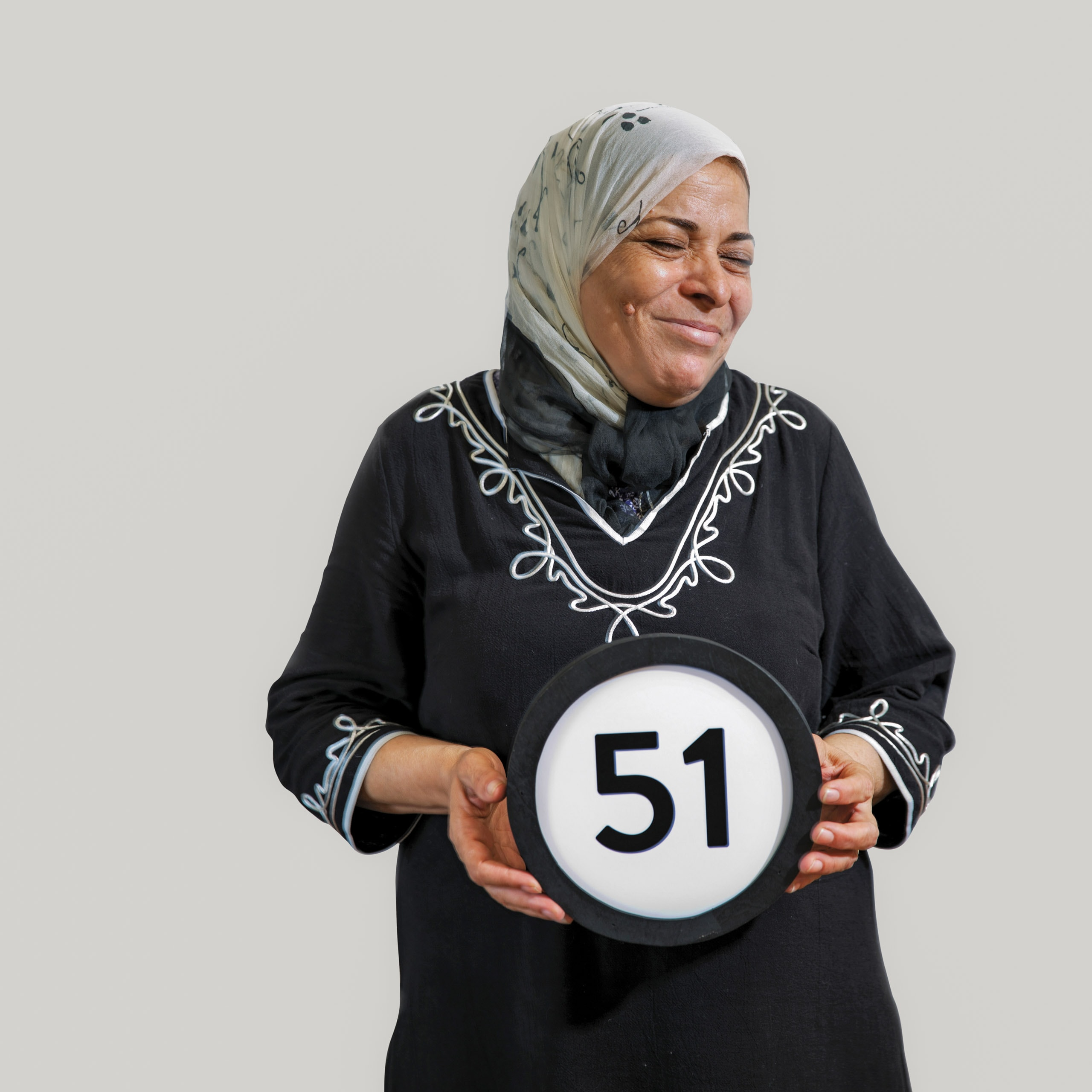 51 year old woman wears a scarf that covers her head and is tied around her neck. Her eyes are closed and she is laughing with her mouth closed. Her black dress has long sleeves and simple curvy embroidery design. She lightly holds a token with the number 51 on it. This digital image is part of the 1 to Infinity portrait photography series by Danny Goldfield.