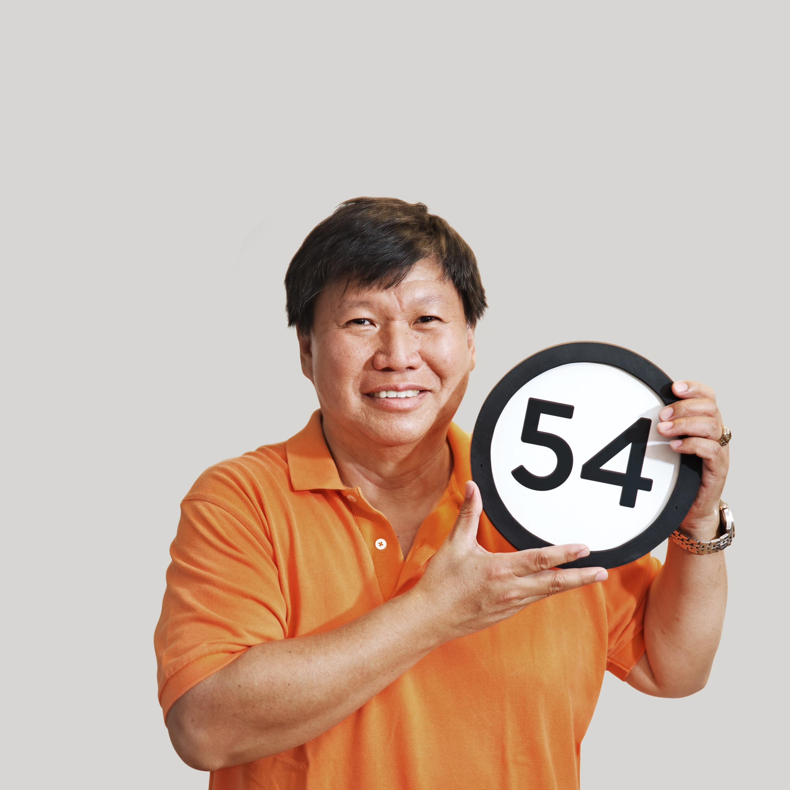 54 year old man wears a bright orange polo shirt and a relaxed smile that spreads across his whole face. His watch looks heavy and there is a college ring on his finger. In his hands just under his left cheek he holds up a token with the number fifty-four on it. This digital image is part of the 1 to Infinity portrait photography series by Danny Goldfield.