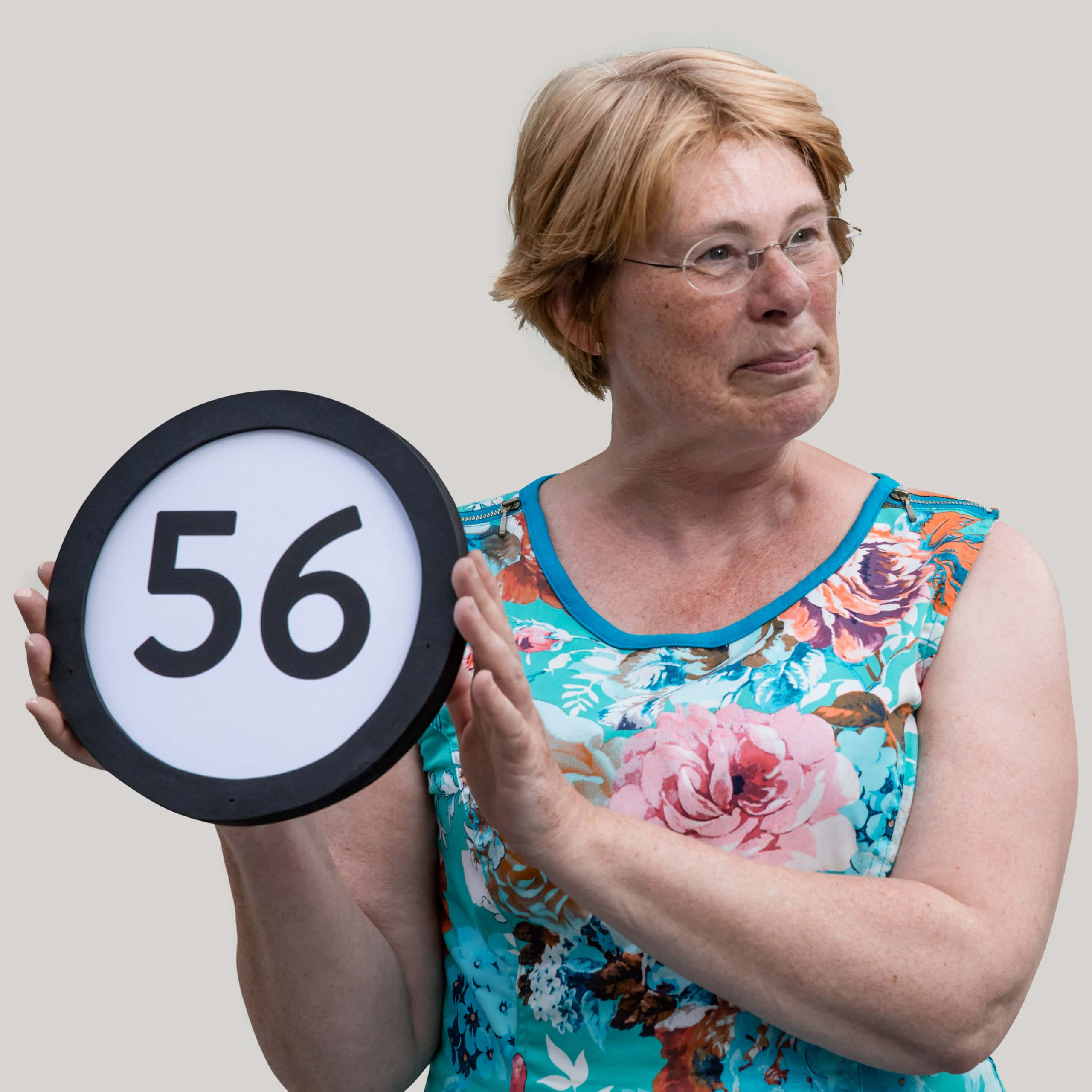 56 year old woman with short red hair and clear glasses wears a floral patterned dress with no sleeves. Her head is turned to her left with a terse but amused expression. To her right she holds up a token with the number 56 on it. This digital image is part of the 1 to Infinity portrait photography series by Danny Goldfield.