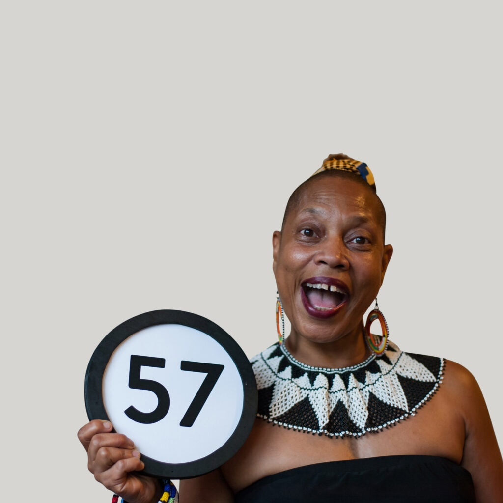 57 year old woman wears a black and white beaded collar, shoulderless dress, an open mouth smile. And she looks into the camera. Her head is shaved, lipstick is dark magenta, and she is thrilled to be holding a token with the number 57 on it. This digital image is part of the 1 to Infinity portrait photography series by Danny Goldfield.