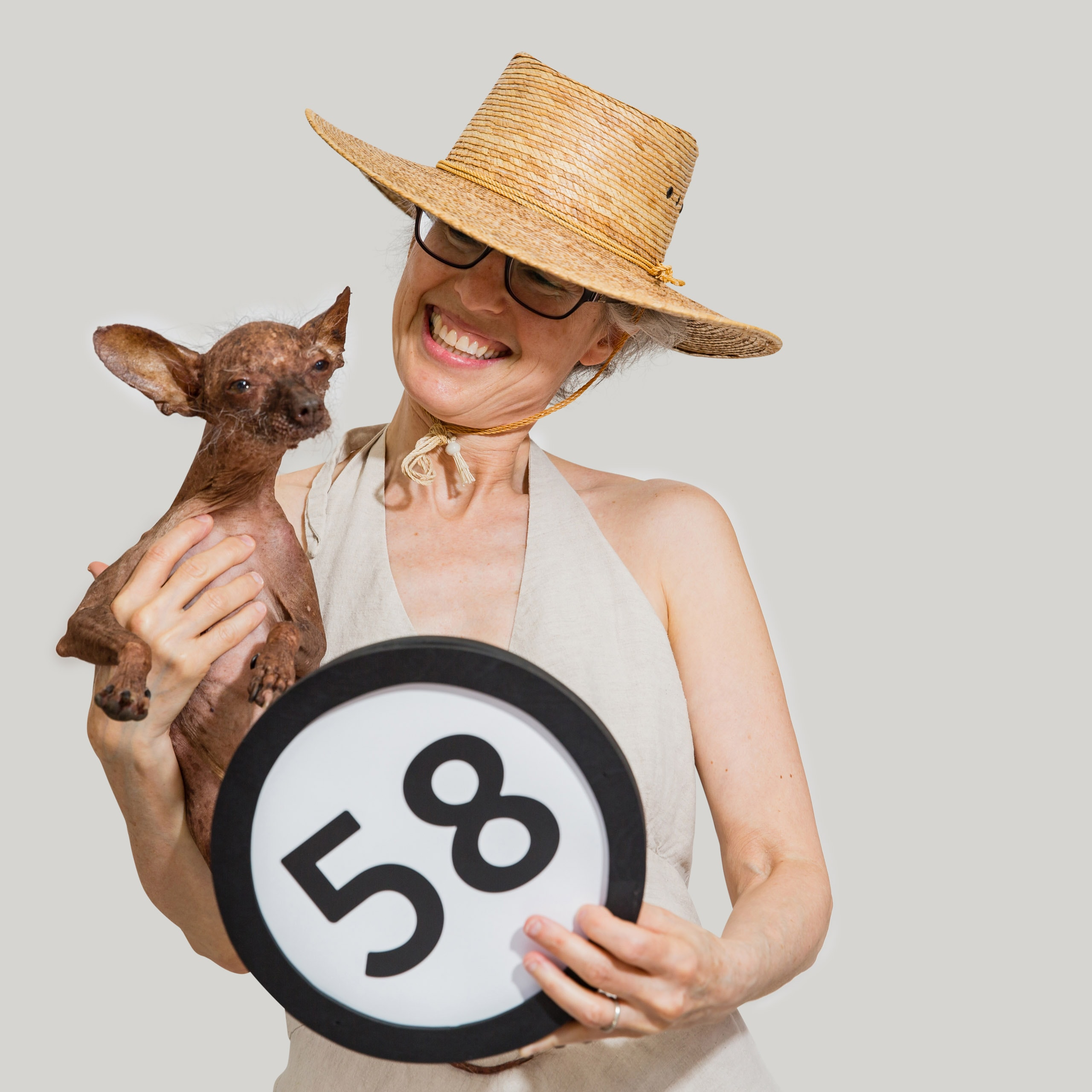 58 years old woman in a big straw sun hat smiles at her hairless alien dog that she holds in her right arm. The alien dog is looking into the lens. The woman also holds a token with the number 58 on it. This digital image is part of the 1 to Infinity portrait photography series by Danny Goldfield