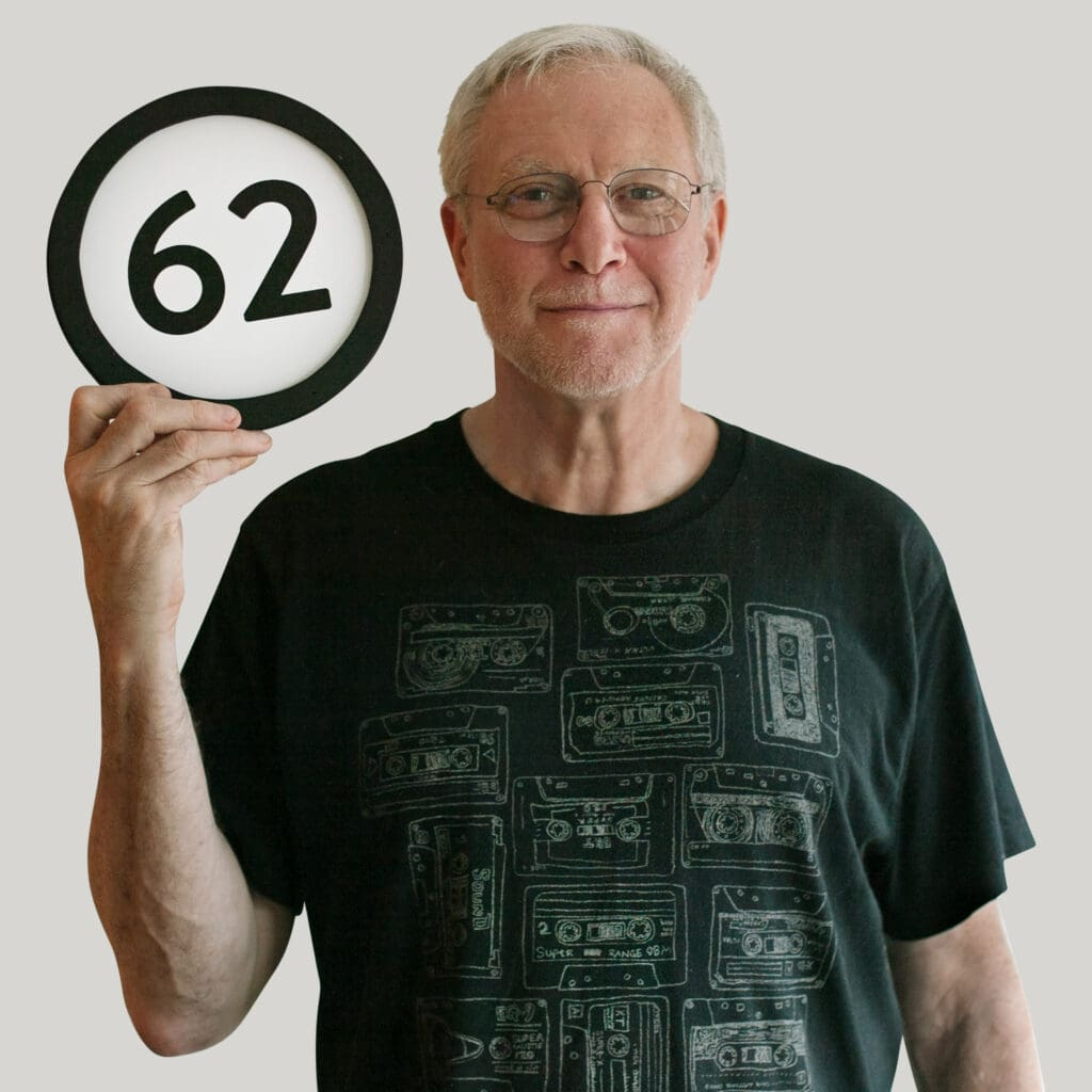 62 year old man wears a black t-shirt with a design of 13 sketches of music cassette tapes. He  has a calm closed smile and looks into the lens through his simple framed eyeglasses. In one hand he holds up a token with the number 62 on it. This digital image is part of the 1 to Infinity portrait photography series by Danny Goldfield