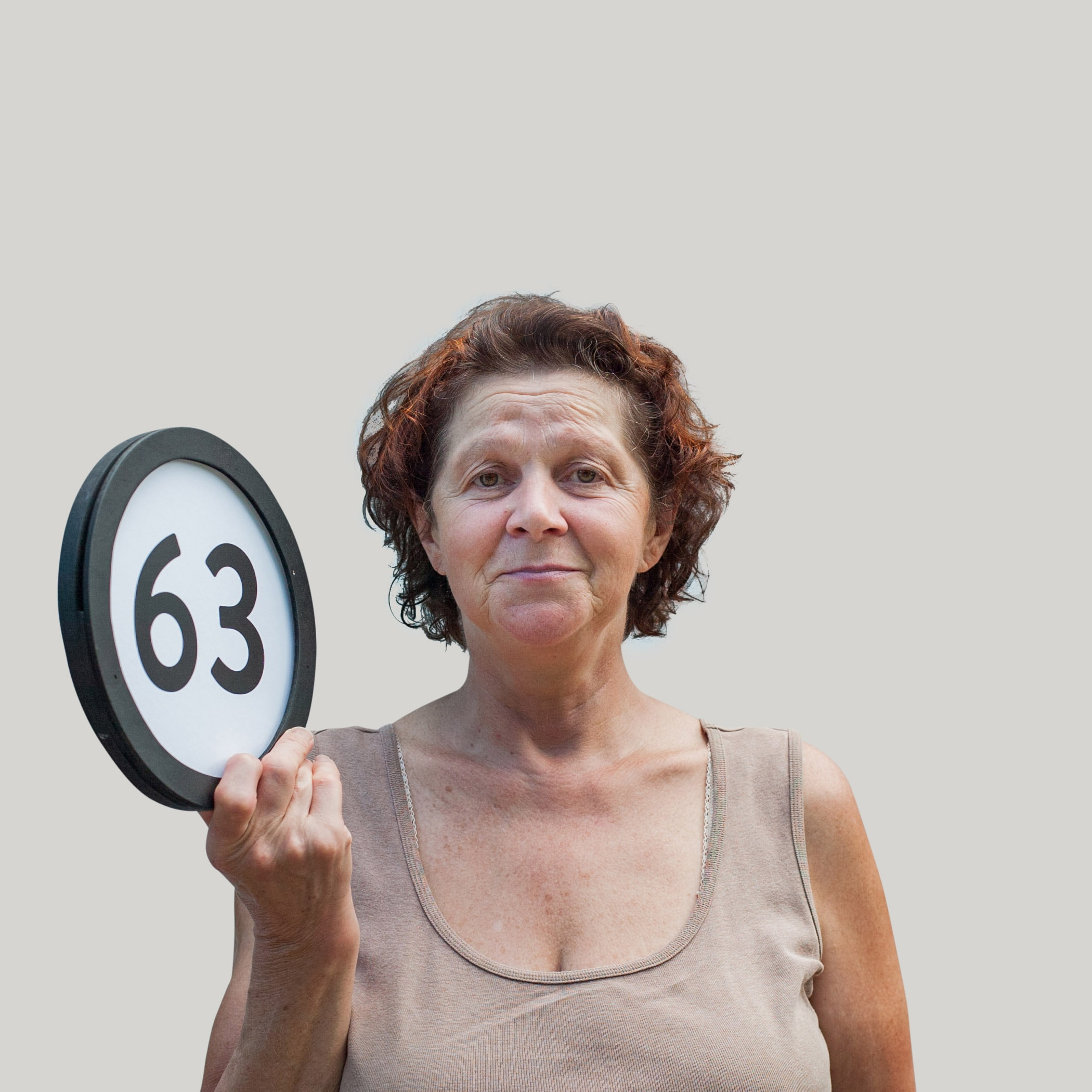 63 year old bemused woman holds with one hand a token with the number sixty-three on it. This digital image is part of the 1 to Infinity portrait photography series by Danny Goldfield..
