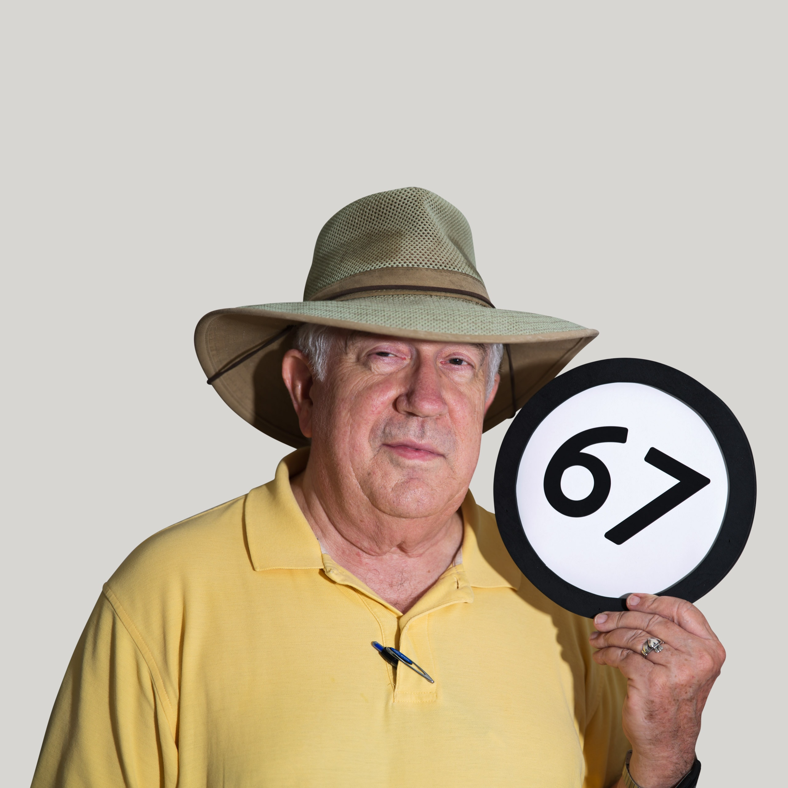 67 year old man wears a worn-in sunhat and faded yellow polo shirt. He looks into the lens with a relaxed expression. A silver Claddagh ring is on the hand that holds up a token with the number 67 on it. This digital image is part of the 1 to Infinity portrait photography series by Danny Goldfield.