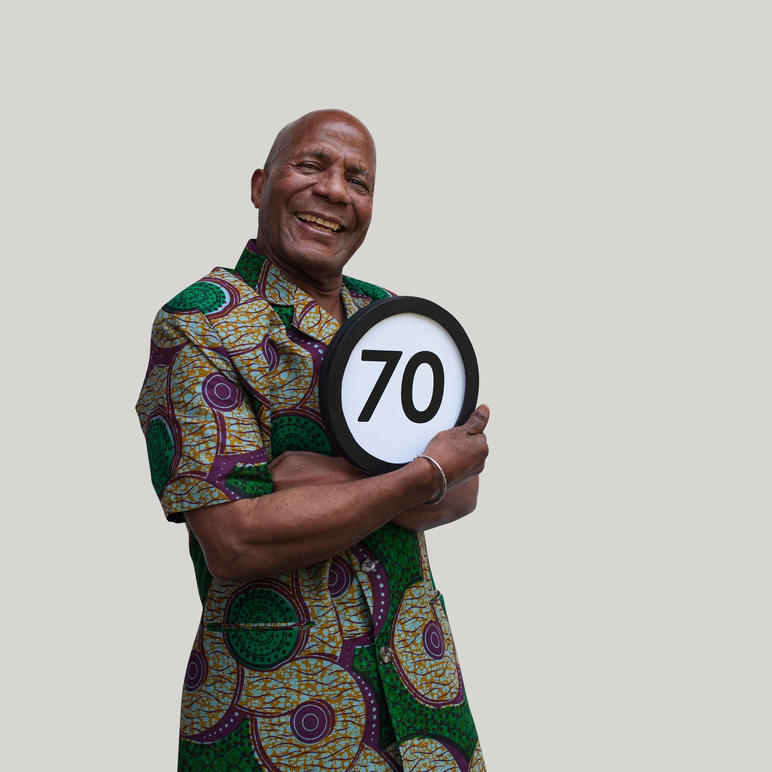 70 your old man wears a colorful summer shirt and smiles broadly into the lens. His arms are folded tightly to his chest and with one hand holds a token with the number 70 on it. This digital image is part of the 1 to Infinity portrait photography series by Danny Goldfield.