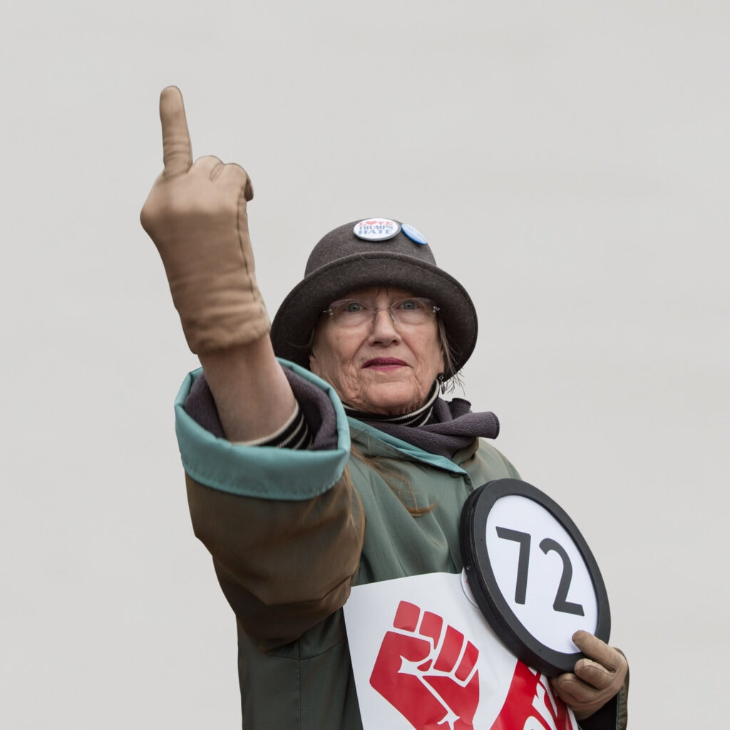 """72 year old woman wears a """"Love Trumps Hate"""" button on her wool cap and directs her middle finger towards the 45th president of the United States of America. Held  over her heart with her other hand is a token with the number 72 on it. This digital image is part of the 1 to Infinity portrait photography series by Danny Goldfield."""