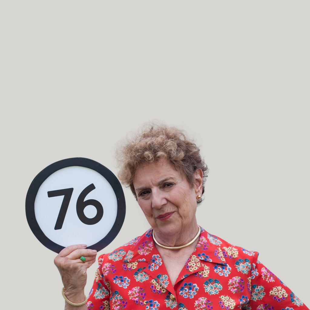 76 year old woman wears a red floral shirt, sleek gold jewelry, and a serious gaze into the lens. With one hand she grips a token with the number 76 on it. This digital image is part of the 1 to Infinity portrait photography series by Danny Goldfield.