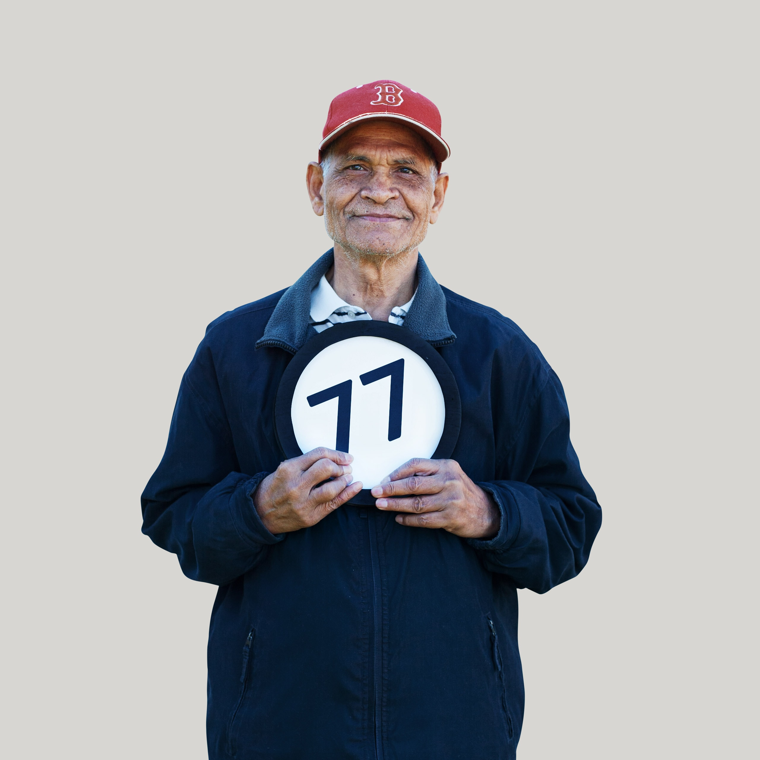 77 year old man wears a baseball cap and a closed mouth smile. He looks directly into the lens  while holding to his chesy a token with the number 77 on it. This digital image is part of the 1 to Infinity portrait photography series by Danny Goldfield.