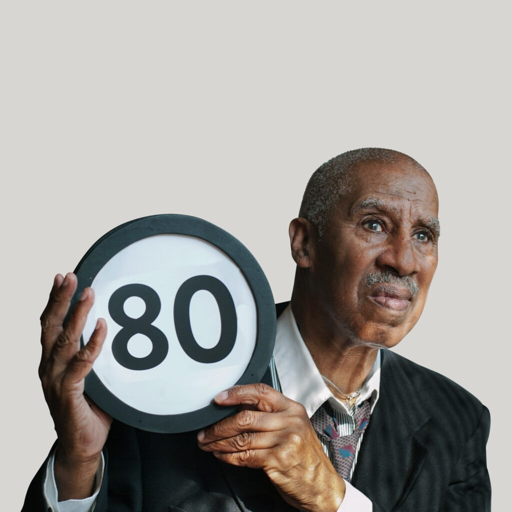 80 year old in an oversized suit jacket and loosened necktie looks concerned. He looks off into the distance while holding up a token with the number 80 on it. This digital image is part of the 1 to Infinity portrait photography series by Danny Goldfield.