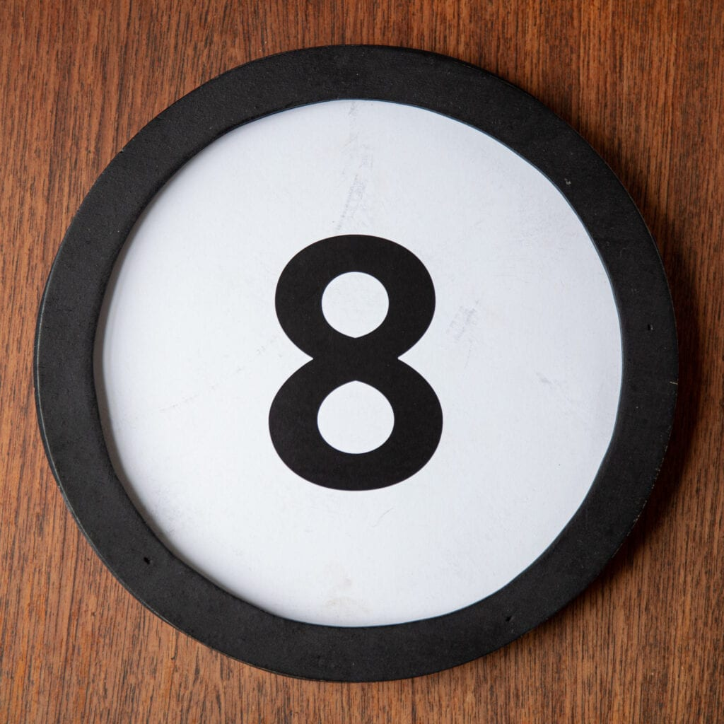A circle shaped token fills the square image. The token has a 1 inch black circular frame around it. In the center is a black number on a white background. The token lies on a teak wood table. This digital image is part of the 1 to Infinity portrait photography series by Danny Goldfield.